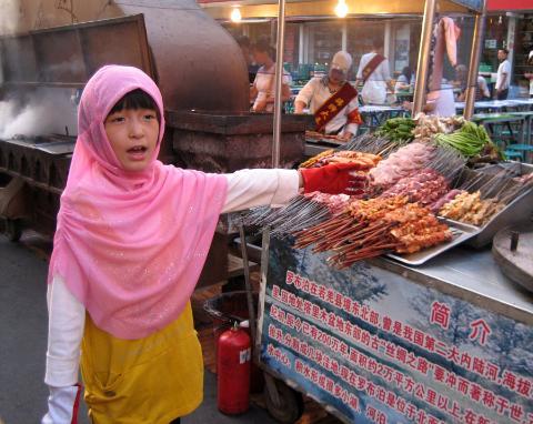 Ein Hui-Mädchen bietet auf dem Nachtmarkt Kebabs an.a
